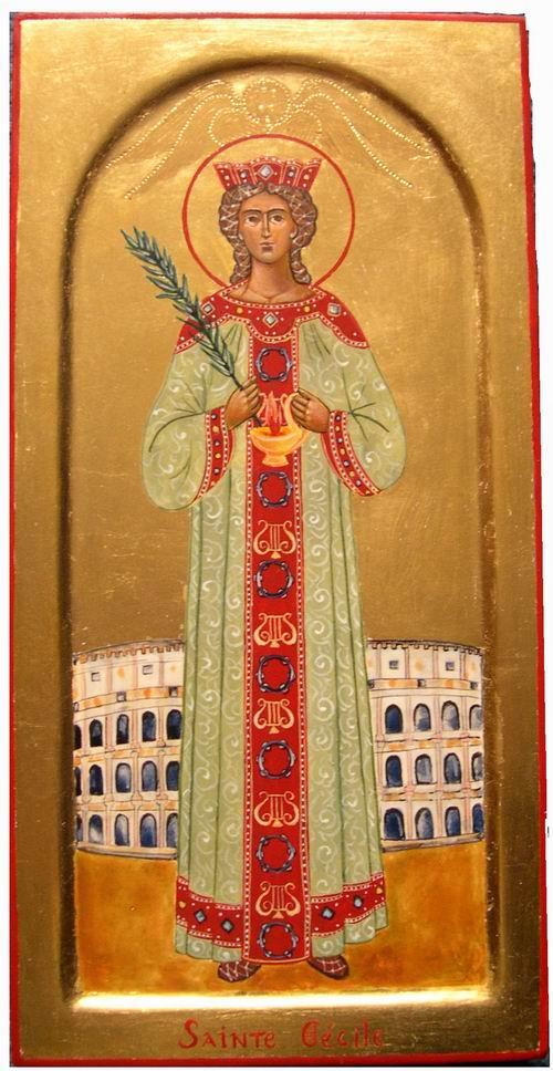 Sainte Cécile est ici représentée dans ses atours de Vierge consacrée ( la lampe fait allusion aux Vierges Sages de l'Evangile qui attendent l'Epoux). Elle porte en main la palme de son martyr et sa robe évoque les robes portées par les femmes martyrs sur les mosaïques paléochrétiennes.